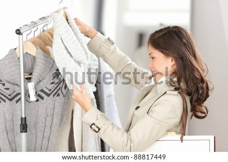 Woman shopping clothes. Shopper looking at clothing indoors in store. Beautiful happy smiling asian caucasian female model. - stock photo