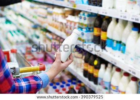 Woman shopping dairy product in grocery store - stock photo