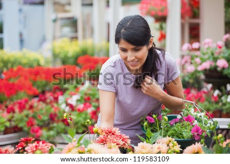 Woman shopping for and looking at plants in garden center - stock photo