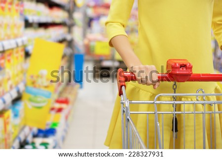 Woman shopping for baby food in supermarket - stock photo