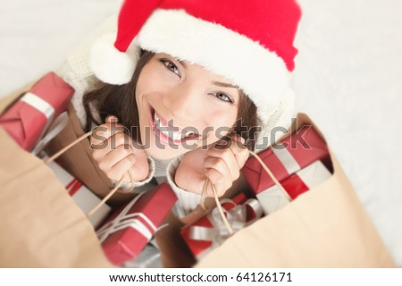 Woman shopping for christmas gifts. Young asian caucasian girl looking up smiling with shopping bags and santa hat. Copy space on the side.