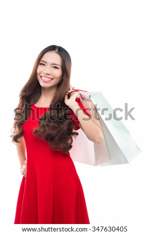 Woman shopping for christmas gifts. Young asian smiling with red dress and shopping bags. Copy space on the side. - stock photo