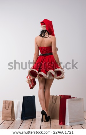 Woman shopping for christmas gifts. Young caucasian girl from behind with shopping bags wearing Santa Claus dress and hat - stock photo