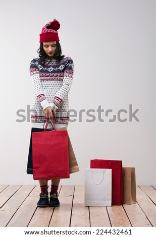 Woman shopping for christmas gifts. Young caucasian girl looking down shy with shopping bags and knitted hat. Copy space on the side. - stock photo
