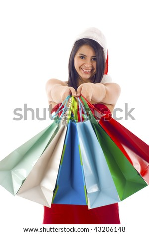 Woman shopping for christmas gifts. Young Hispanic / Latin American girl smiling with shopping bags and santa hat. Copy space on the side.