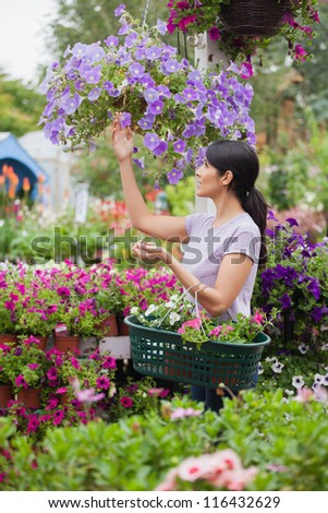 Woman shopping for flowers in garden center carrying basket - stock photo