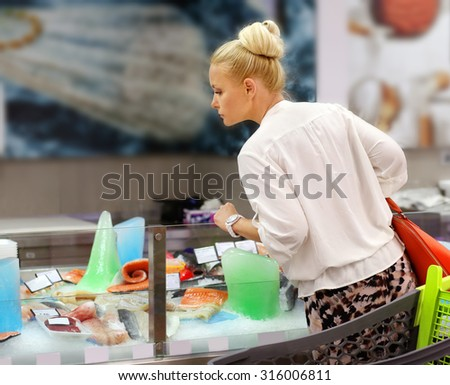 Woman shopping for fresh fish seafood in supermarket retail store  - stock photo