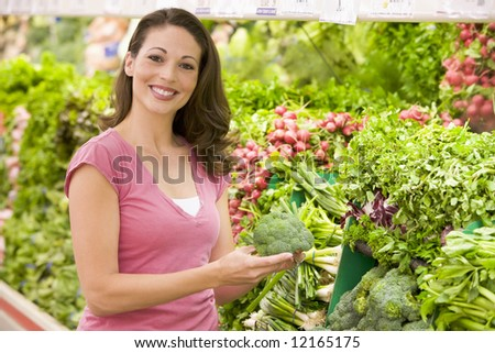 Woman shopping for fresh vegetables in supermarket - stock photo