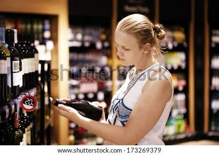 Woman shopping for wine or other alcohol in a bottle store standing in front of shelves full of bottles and holding bottle in her hand and reading inscription - stock photo