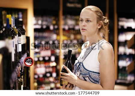 Woman shopping for wine or other alcohol in a bottle store standing in front of shelves full of bottles with a serious expression as she tries to make up her mind - stock photo