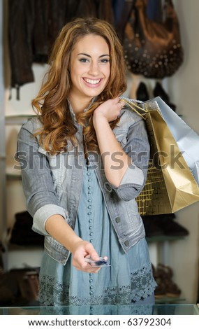Woman shopping in a cloth shop paying with a credit card - stock photo
