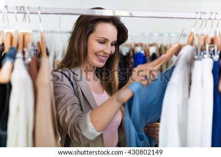 Woman shopping in a clothing store   - stock photo