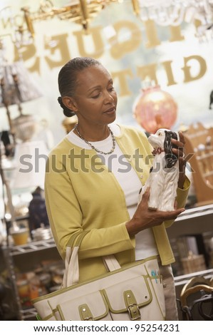 Woman shopping in antique store - stock photo