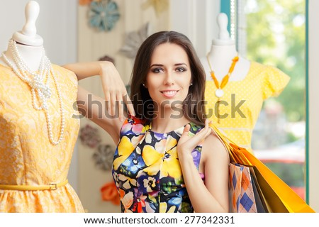 Woman Shopping in Fashion Store - Young girl shopping for yellow dresses in fashion boutique   - stock photo