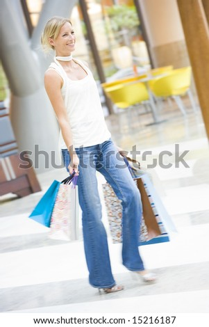 Woman shopping in mall with bags - stock photo