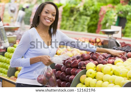 Woman shopping in produce department of supermarket - stock photo