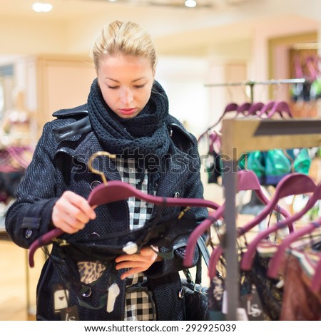 Woman shopping lingerie . Shopper looking and choosing clothing indoors in store. Beautiful blonde caucasian female model wearing winter coat and fashionable knitted shawl. - stock photo