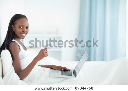 Woman shopping online in her bedroom