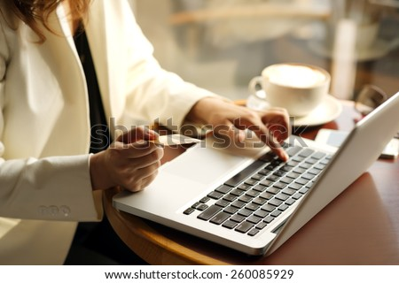 Woman shopping online in the cafe - stock photo