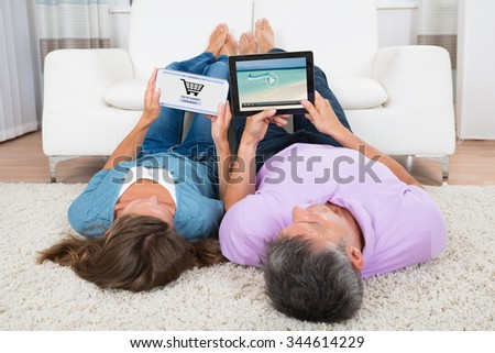 Woman Shopping Online On Digital Tablet While Man Watching Video In Living Room - stock photo