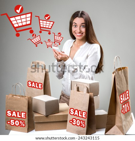 Woman shopping online with smart phone with shopping bags and graphic baskets on background - stock photo