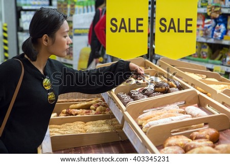 Woman shopping pastry at the supermarket - stock photo