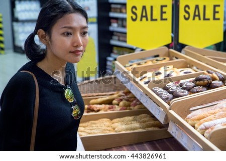 Woman shopping pastry at the supermarket. The customer chooses fresh pastry from the store offer. Discount - Sale pastries in the shop. - stock photo