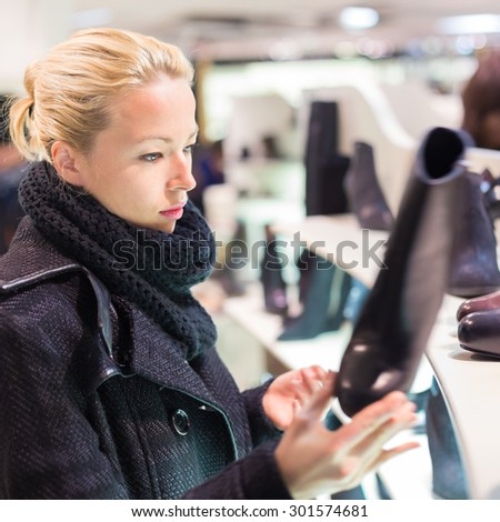 Woman shopping shoes. Shopper looking at ancle high boots on display shelf in shoe store. Beautiful blonde caucasian female model.  - stock photo