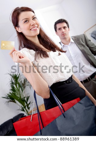 Woman shopping with her boyfriend's credit card - couple's lifestyle - stock photo