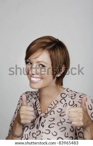 woman shot in the studio given her thumbs up to say all is good - stock photo