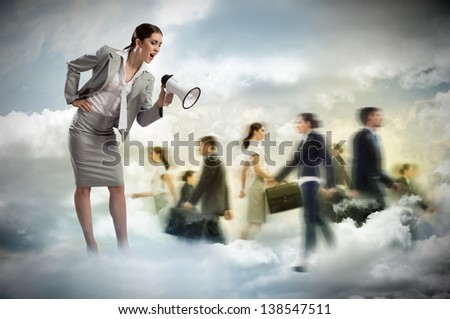 woman shouting into a megaphone at the crowd of business people, the concept of aggression - stock photo
