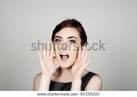 woman shouting out with hands up to face - stock photo