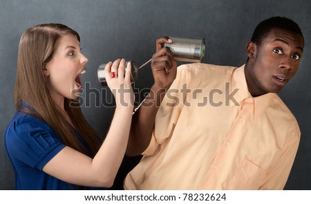 Woman shouts at a man through stringed cans on gray background - stock photo