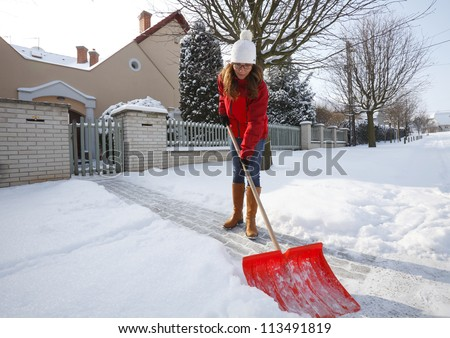 Woman shoveling and removing snow in front of her house in the suburb - stock photo