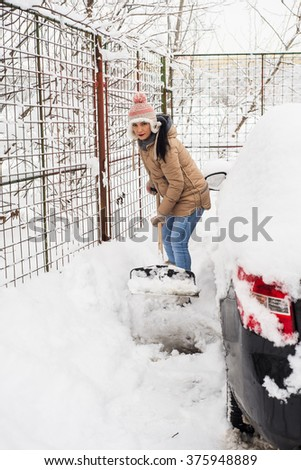Woman shoveling snow around car  in a cold day - stock photo