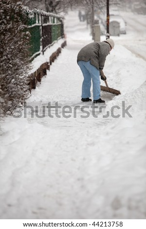 Woman shoveling snow from the sidewalk in front of her house after a heavy snowfall in a city - stock photo