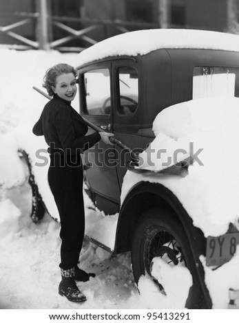 Woman shoveling snow off car - stock photo
