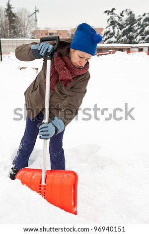 Woman shoveling snow off sidewalk. - stock photo