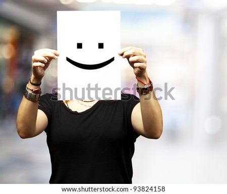 Woman showing a blank paper with a smile emoticon in front of her face at a crowded place - stock photo