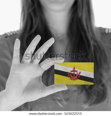 Woman showing a business card, flag of Brunei - stock photo