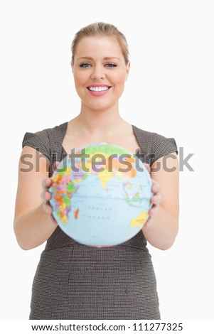 Woman showing a globe against white background