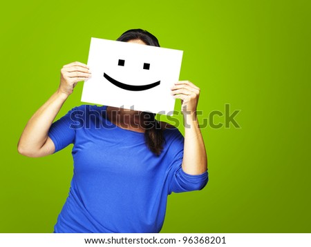 Woman showing a happy emoticon in front of face against a green background - stock photo