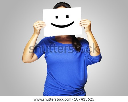Woman showing a happy emoticon in front of face over a grey background - stock photo