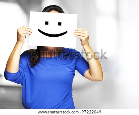 Woman showing a happy emoticon in front of her face indoor - stock photo