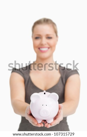 Woman showing a piggy bank against white background - stock photo