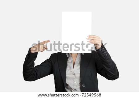 Woman showing and pointing to a  blank paper sheet in front of her head