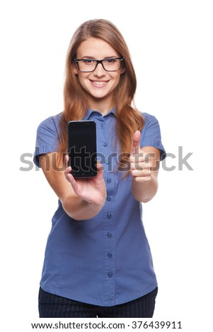 Woman showing blank black smart phone screen and giving an approval sign, over white background. Shallow depth of field, focus on the phone. - stock photo