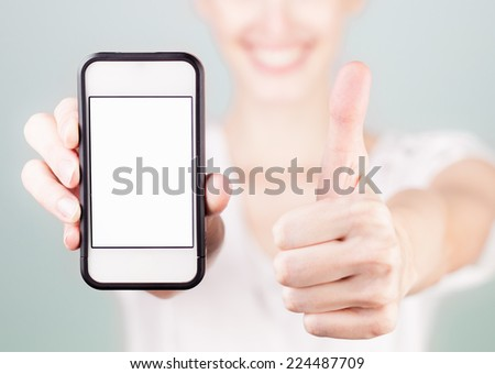 Woman showing blank smart phone with thumbs up - stock photo