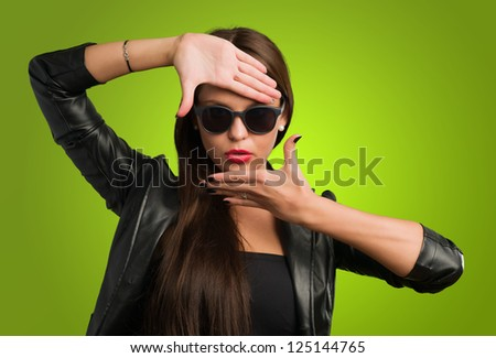 Woman Showing Finger Frame against a green background - stock photo