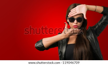 Woman Showing Finger Frame against a red background - stock photo